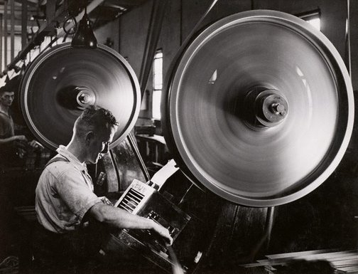 An image of Untitled (man and machine wheel) by Max Dupain