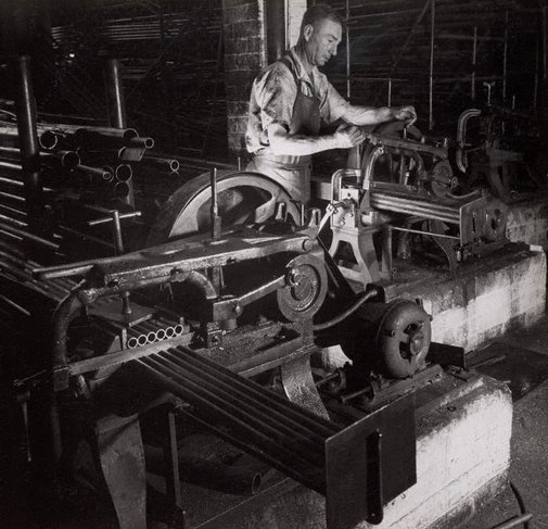 An image of Untitled (man with pipe cutting machine) by Max Dupain