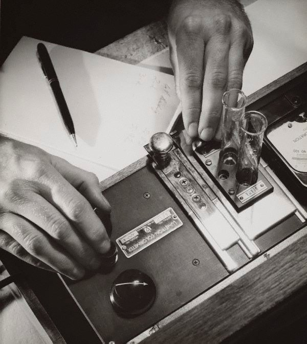 An image of Untitled (hands operating a Lumetron Colorimeter)