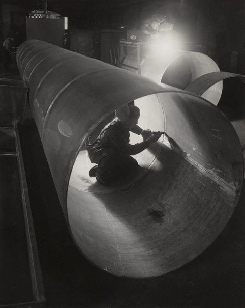An image of Untitled (man working on inside of pipe) by Max Dupain