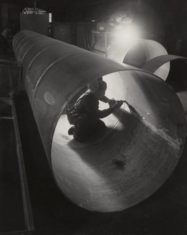An image of Untitled (man working on inside of pipe)