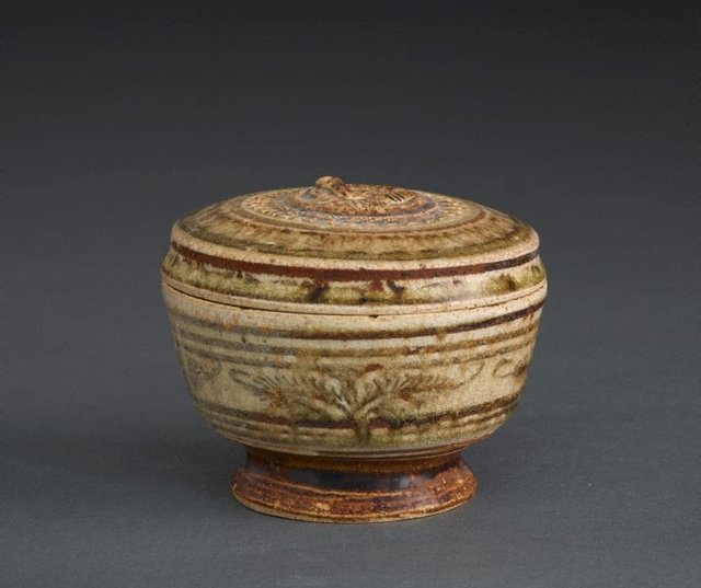 An image of Footed jar with lid and carved decoration, as well as floral and geometric patterning