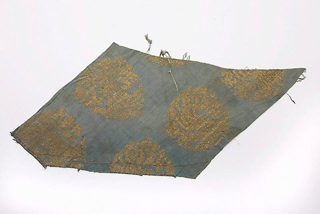 An image of A fragment of Chinese woven silk depicting phoenixes soaring among clouds