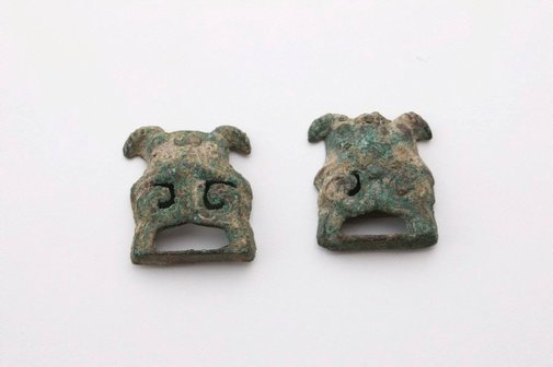 An image of Pair of buckles in the form of taoist masks with some openwork by