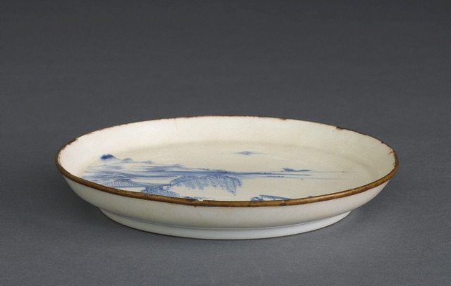 An image of Plate with a landscape scene of building, boats, and mountains