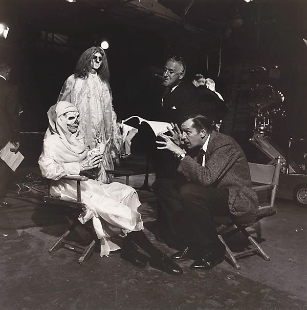 "An image of Director, William Castle, listens as star Vincent Price tells a chilling story to two members of the cast of the movie, ""Ghoulie, 13 Ghosts"""