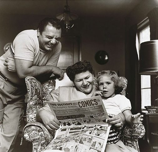 An image of Ernest Borgnine with his wife Rhoda and daughter Nancee read the comics taken in 1955 for The Saturday Evening Post by Sid Avery