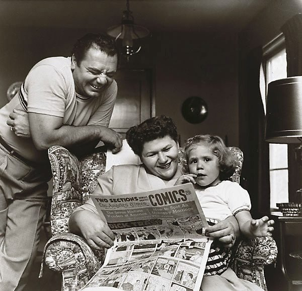 An image of Ernest Borgnine with his wife Rhoda and daughter Nancee read the comics taken in 1955 for The Saturday Evening Post