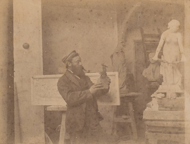 An image of Untitled (portrait of a man with pipe holding a sculpture)