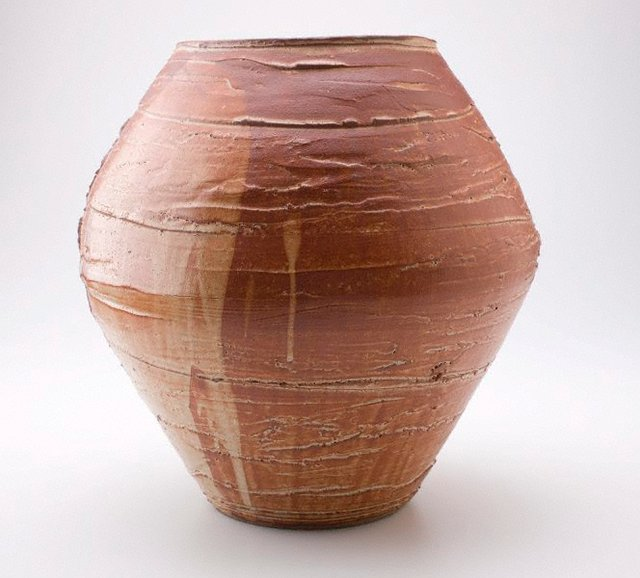 "An image of Floor vase with red ""shino"" glaze and design of incised pampas grass"