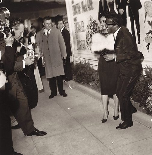 An image of Sammy Davis Jr., and his wife, Laray White Davis at the Hollywood Premiere of 'Can Can'; leaning forward is leading Hollywood photographer Nat Dillinger by Sid Avery