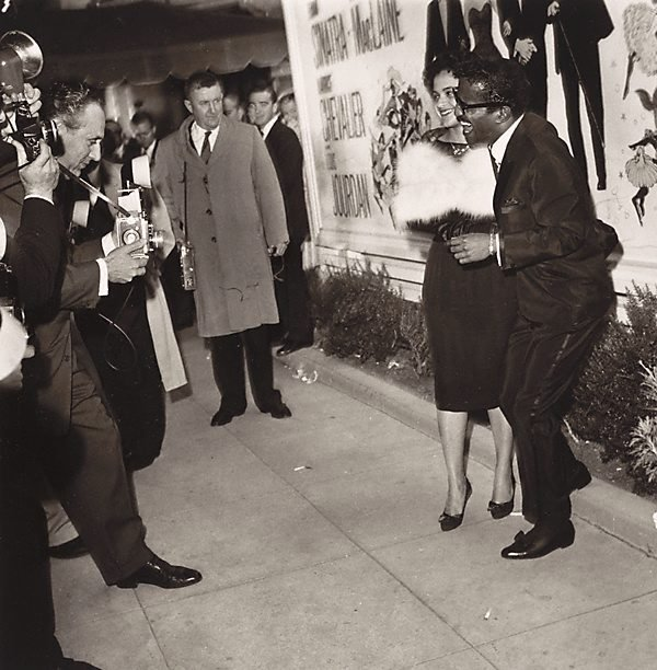 An image of Sammy Davis Jr., and his wife, Laray White Davis at the Hollywood Premiere of 'Can Can'; leaning forward is leading Hollywood photographer Nat Dillinger