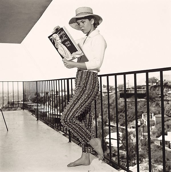 An image of Tuesday Weld looking at a Tuesday Weld Cut Out Doll Book on the balcony of her Los Angeles Home