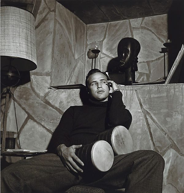 An image of Marlon Brando with bongo, and African mask