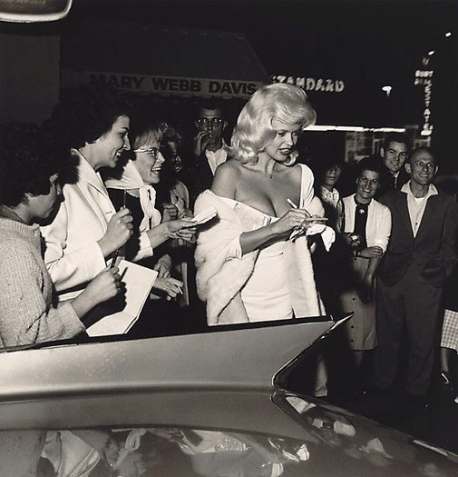An image of Jayne Mansfield signing autographs in front of Dino's restaurant on the Sunset Strip in Los Angeles. Photographed in 1961 by Sid Avery