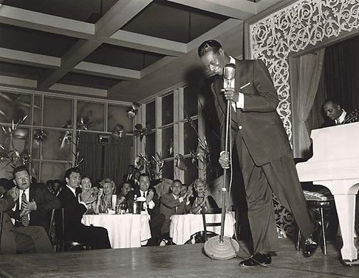 "An image of Nat ""King"" Cole performs at Ciro's Night Club. In the audience Jack Palance (left) and Gig Young (right) by Sid Avery"