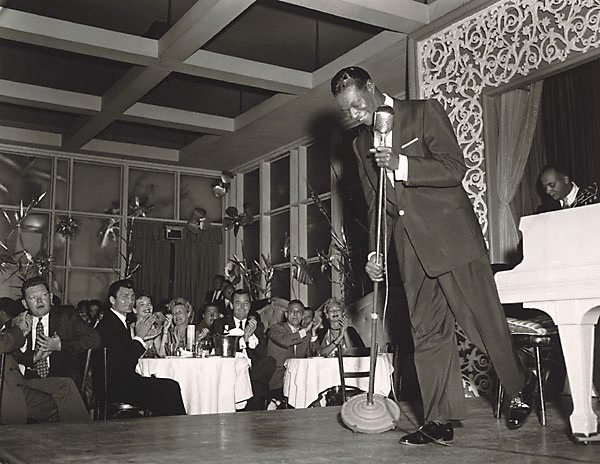 "An image of Nat ""King"" Cole performs at Ciro's Night Club. In the audience Jack Palance (left) and Gig Young (right)"