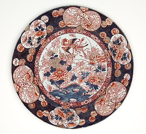 An image of Large charger with design of phoenix and flowering plants in the centre and flower and animal pattern around it by Arita ware