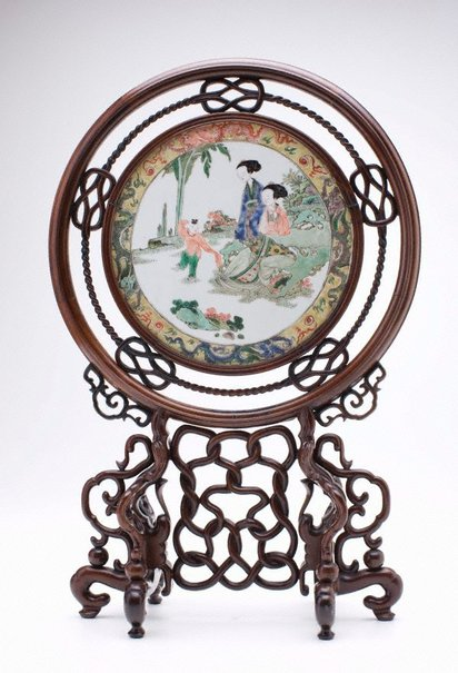 An image of Circular tile with scene of two ladies and a child by