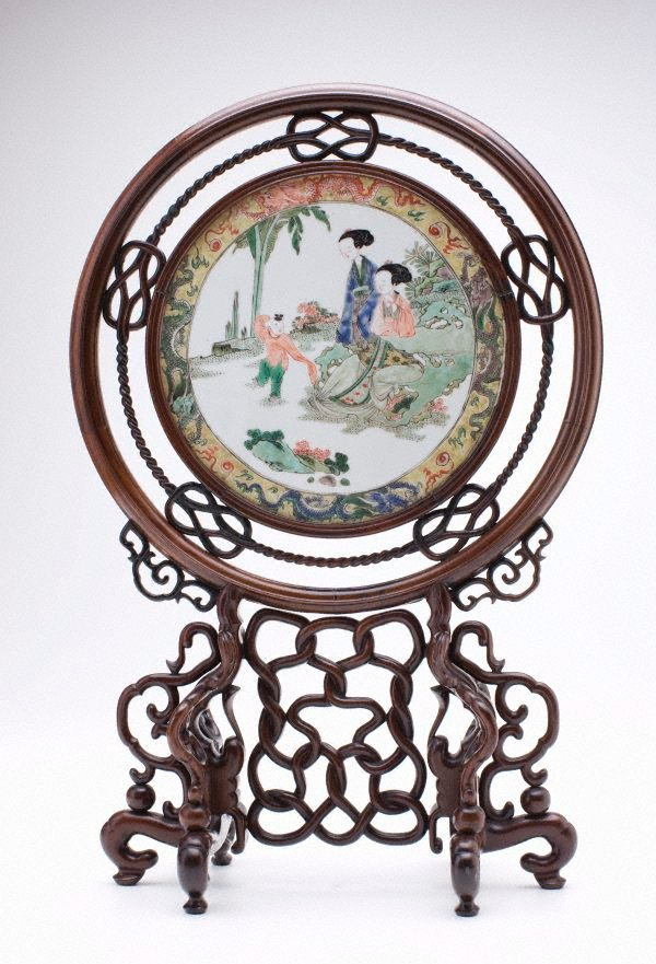 An image of Circular tile with scene of two ladies and a child