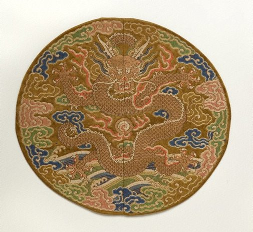 An image of Front facing dragon roundel with brown background by