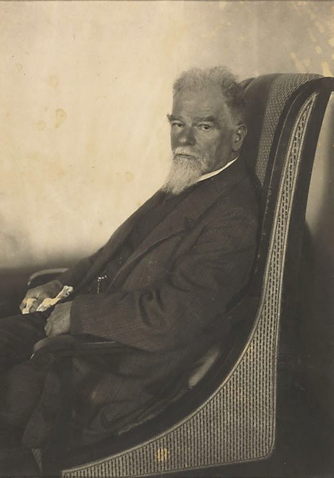 An image of Max Klinger in three-quarter profile seated in an armchair