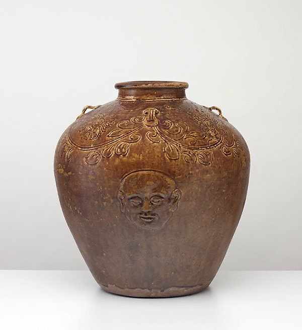 An image of Globular jar decorated with relief 'head and hand' motif