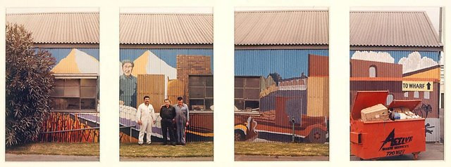 An image of Untitled (3 men standing against mural on factory wall. Orange garbage bin on right)  Yarraville sugar refinery