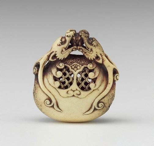 An image of Netsuke in the form of two dragon heads encircling a bell by