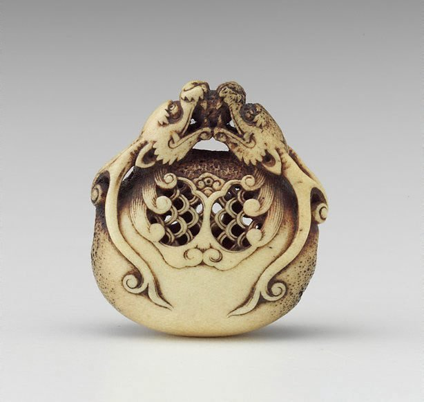An image of Netsuke in the form of two dragon heads encircling a bell
