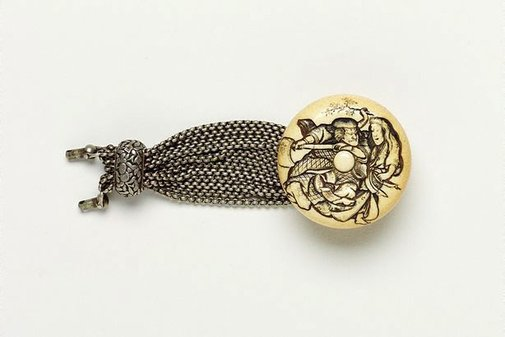 An image of 'Manju' netsuke of woodcutter and woman, with multiple silver chains [which originally would have attached it to a tobacco pouch] by