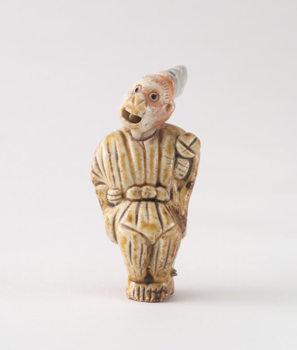 An image of Netsuke in the form of a monkey dressed as a court noble
