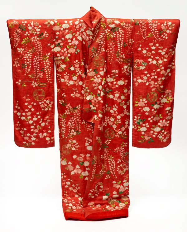 An image of Furisode uchikake (long-sleeve overcoat) with design of plum and cherry blossoms, peonies, chrysanthemums and wisteria on red figured silk satin ('rinzu')
