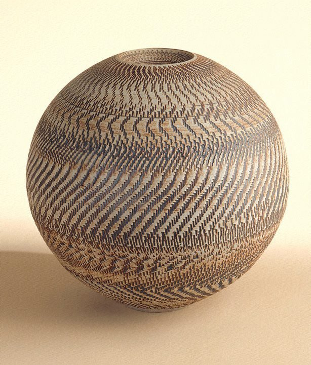 An image of Round unglazed pot with iron oxide colouring and chattered decoration