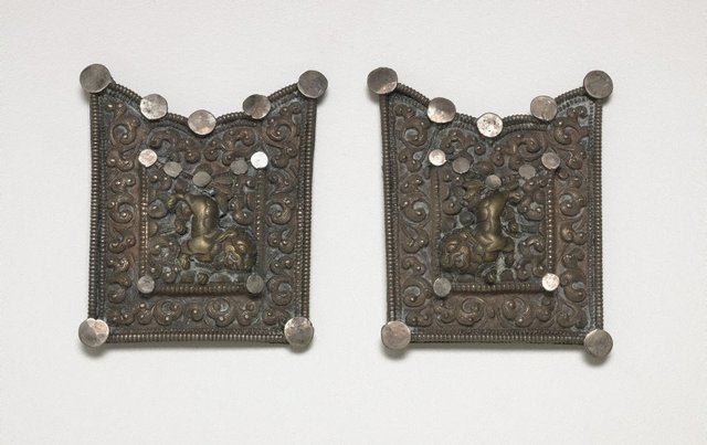 An image of A two part belt buckle or harness fitting depicting a pair of snow lions