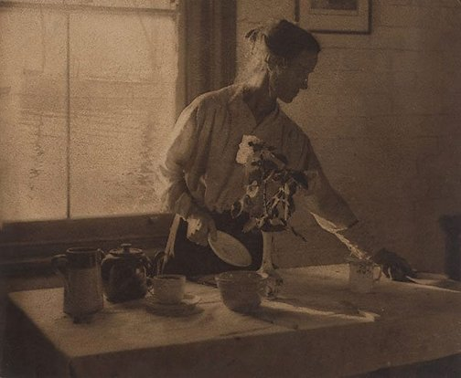An image of Untitled (Woman in kitchen) by Alfred Chambers