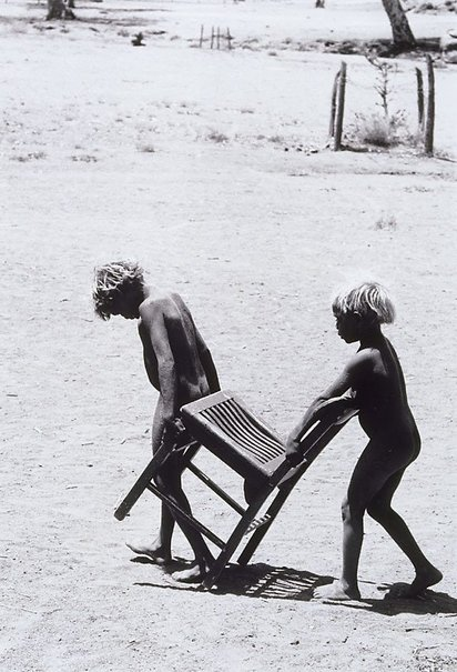 An image of Pitjantjatjara children with chair, South Australia by David Moore