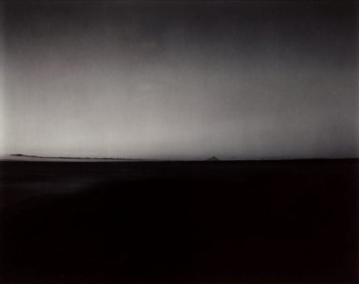 An image of A distant view of Taranaki from the mouth of the Wanganui river, at dusk, 3 February 1986 by Laurence Aberhart