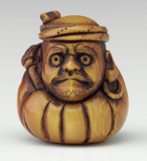 An image of Netsuke in the form of Daruma with a fly whisk, wearing a towel round his head by