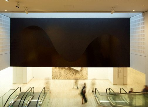 An image of Wall drawing #870: A black wall divided horizontally by a wavy line. Top: flat; bottom: glossy by Sol LeWitt