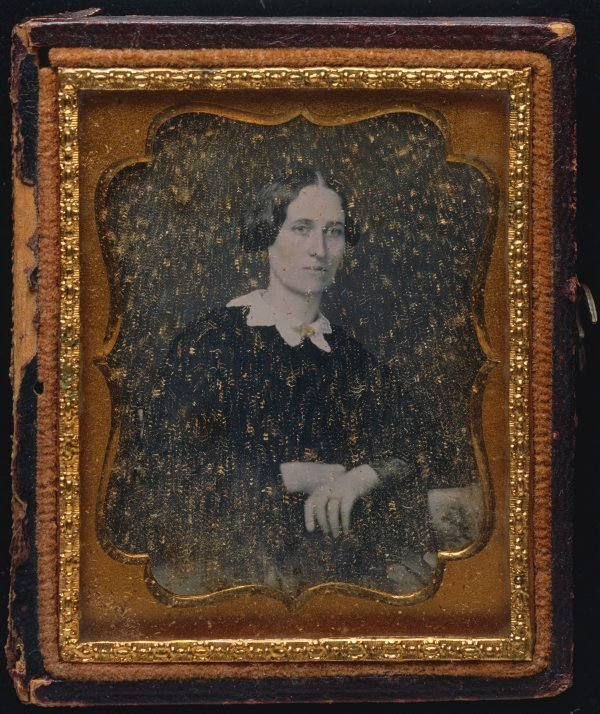 An image of Untitled (Woman with grim expression, hands folded)