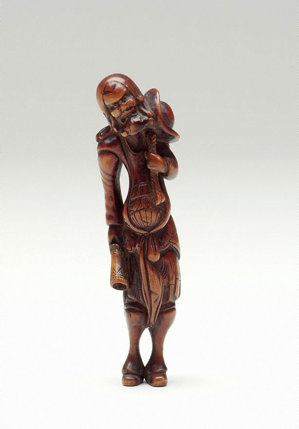 An image of Netsuke in the form of a Dutchman with a hat, holding a horn
