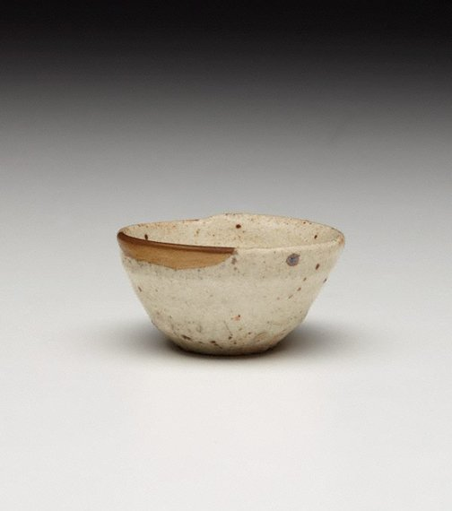 An image of Sake cup with gold lacquer mending by Shino ware
