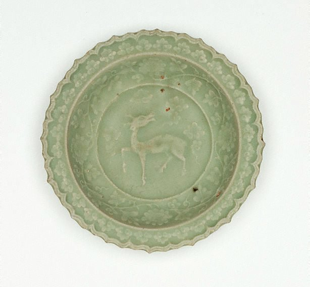 An image of Saucer dish with slip design of antelope and foliate edge