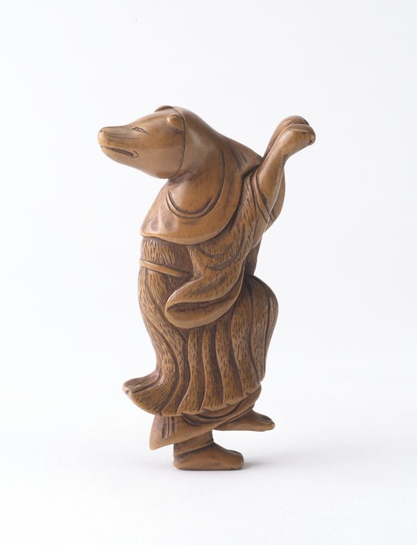 An image of Netsuke in the form of a fox disguised as a woman dancing