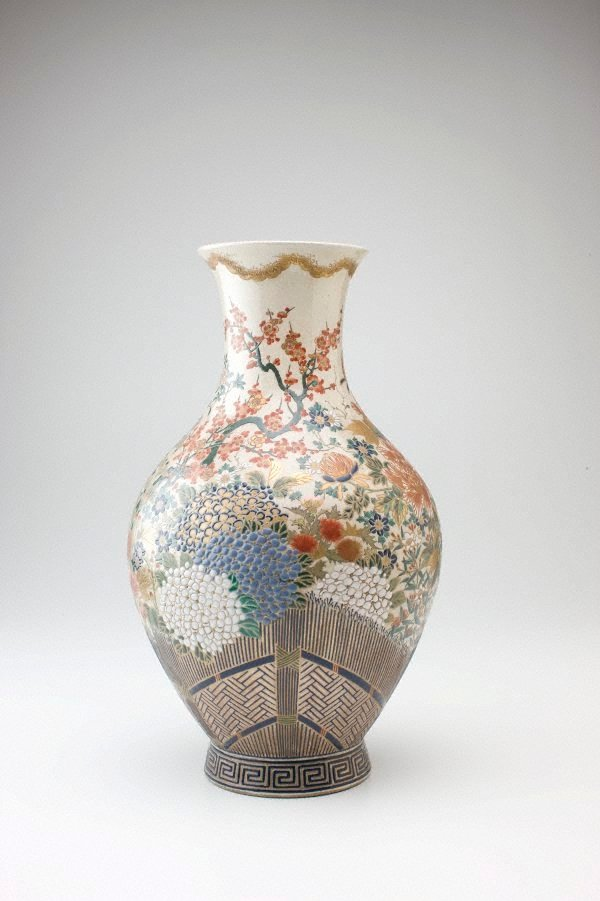 An image of Vase with design of flowers and thatched fence