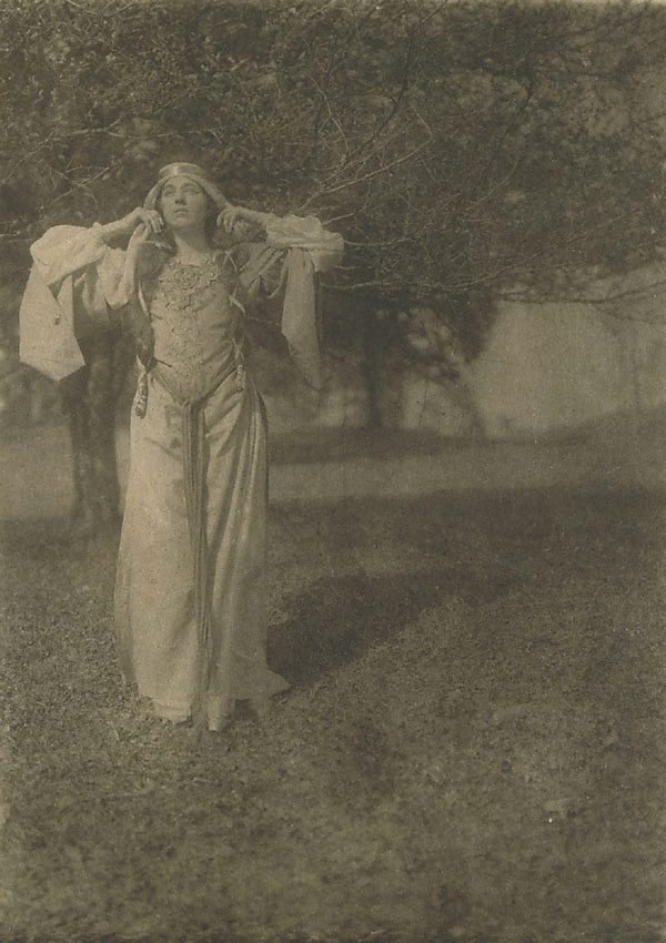 An image of Illustration no 18 (woman in medieval garb with hands raised to ears, searching in wood from Arthurian legend) from Camera Work, no 27, July 1909