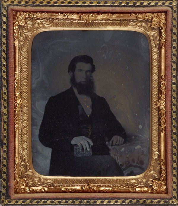 An image of Untitled (unknown man with dark hair and beard, gold watch chain, rings and shirt studs, holding an ambrotype? with Ottoman embroidered table cloth)