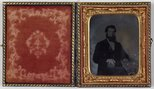 Alternate image of Untitled (unknown man with dark hair and beard, gold watch chain, rings and shirt studs, holding an ambrotype? with Ottoman embroidered table cloth) by Unknown