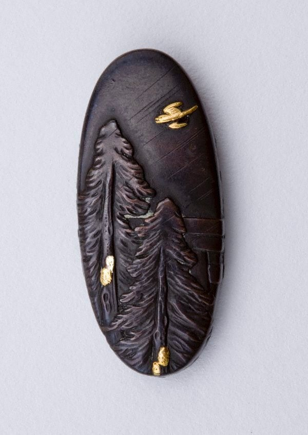 An image of kashira (with design of fir trees and bird in flight)